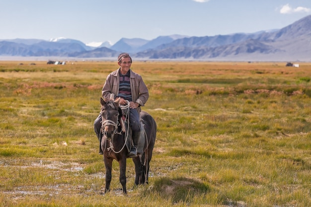 The mongolian horseman stopped, looking at tourists and laughing at them