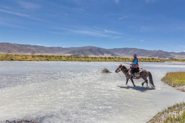 Mongolian nomad crosses a white mountain river on a horse.