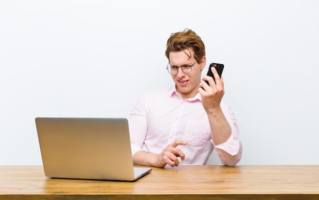 Молодой рыжий бизнесмен работает в своем столе с телефоном monile