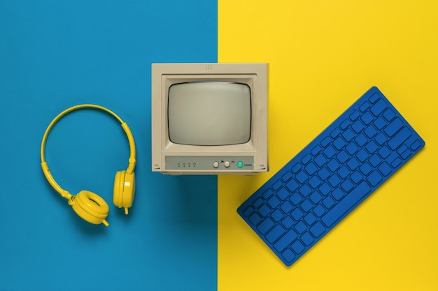 A monitor, a blue keyboard and yellow headphones on a yellow and blue background. vintage equipment. flat lay.