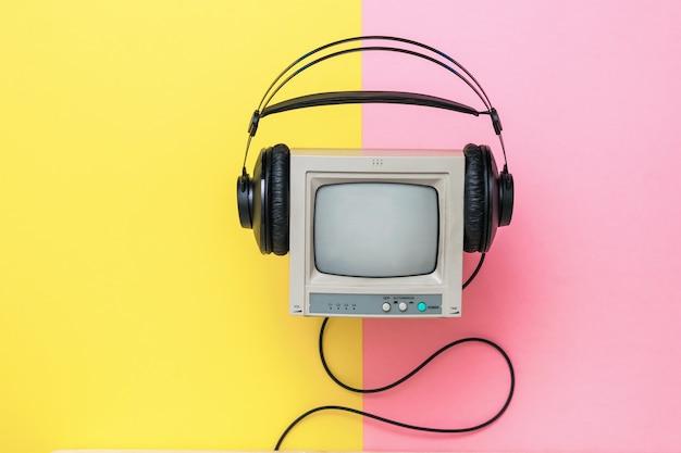 Монитор для видеонаблюдения и наушники на цветном фоне. техника воспроизведения звука и видео.