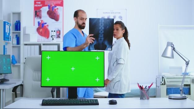 의사와 간호사가 엑스레이 이미지를 확인하는 동안 크로마 키가 있는 병원 캐비닛을 모니터링합니다. 의사가 진단을 위해 환자 방사선 사진을 확인하는 동안 의료 클리닉에서 교체 가능한 화면이 있는 데스크탑.