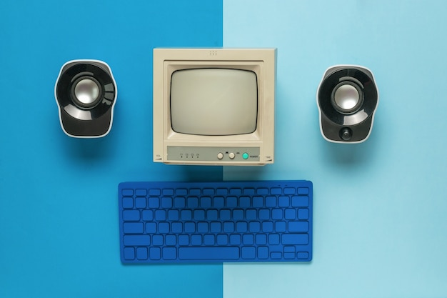 A monitor, a keyboard and two computer speakers on a two-tone blue background. flat lay.