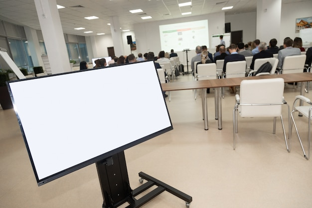 Monitor showing development plan organization against audience inconference room