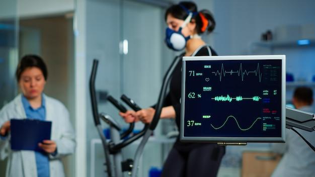 クロストレーナーと医療専門家で走っているアスリートのekgスキャンを示すモニターは、バックグラウンドでの運動を監督し、身体活動を制御し、スポーツ科学研究所で心拍数を測定します
