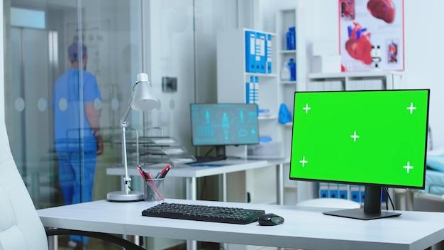 남성 조수가 엘리베이터를 기다리는 동안 병원에서 녹색 화면으로 모니터링합니다. 클리닉 캐비닛의 의학 전문가가 사용할 수 있는 빈 공간이 있는 컴퓨터.