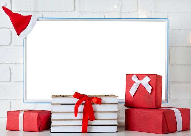 복사 공간이 있는 흰색 화면과 책 및 기타 선물 상자 옆에 있는 모니터.