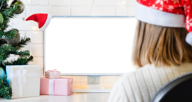 Monitor with white screen with copy space and gifts and blurry silhouette of the girl.