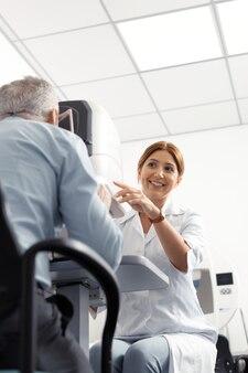視力のモニタリング。男の視力を監視しながら笑っている赤毛の晴れやかな目の専門家