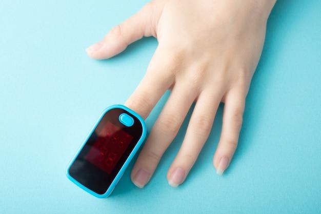 青い背景の女性の指の特別なデバイスで血液の酸素飽和度を監視する