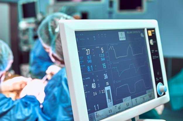 Мониторинг жизненно важных функций пациента в операционной в фокусе. на backgdound blured хирургии уменьшение черепа увеличение двойной подбородок