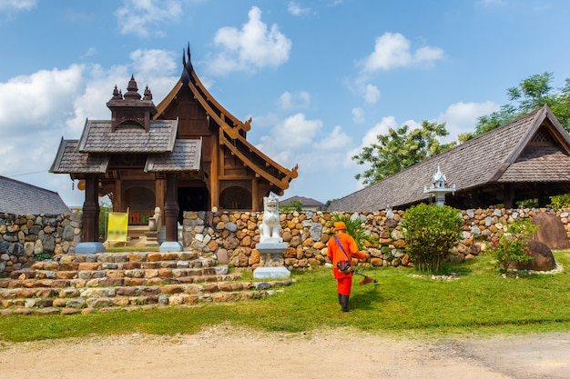 Monk cutting grass in garden around the temple in countryside of northern thailand