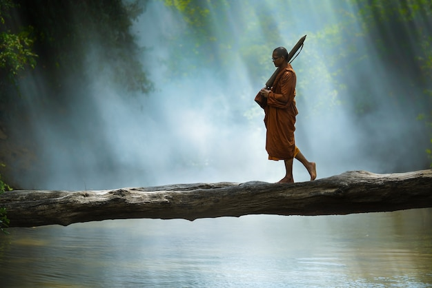 Monk hiking cross the river in forest,thailand,