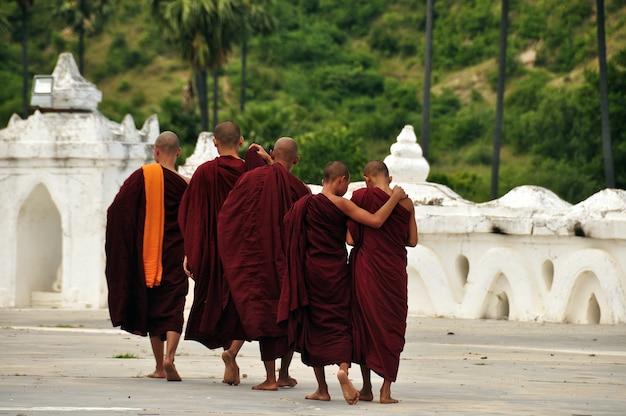 Монах в храме синбюмэ пая, группа монахов в традиционных красных одеждах. бирма, мьянма, мандалай.
