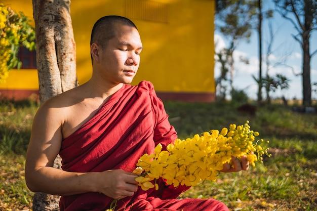 花と瞑想する僧侶。