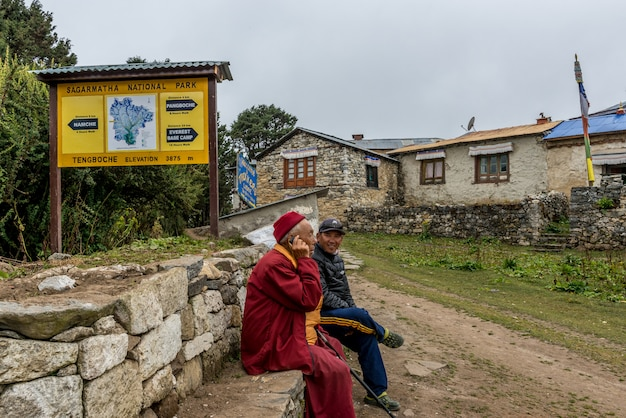 Monk and nepalese local man sit on rock wall use mobile communicate in tengboche,nepal