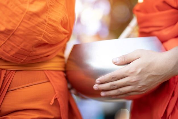 Монах с рукой держит чашу для подаяний, которая вышла из подношений утром в буддийском храме