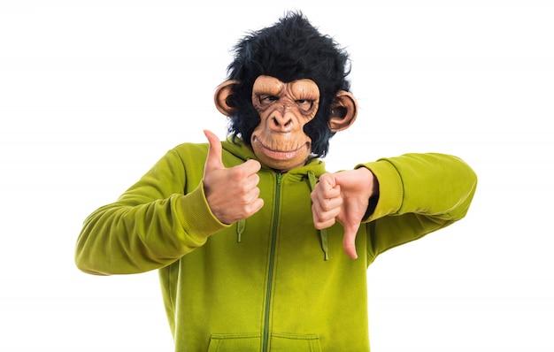 Uomo di scimmia che fa il segno buono-cattivo