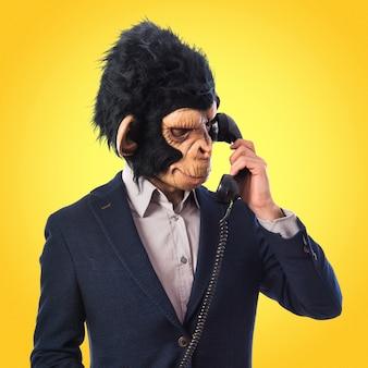Человек-обезьяна разговаривает с старинным телефоном на цветном фоне