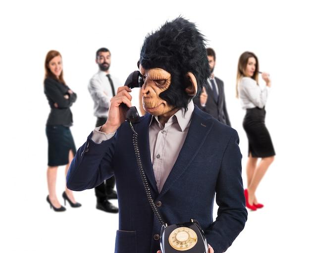 Человек-обезьяна разговаривает со старинным телефоном