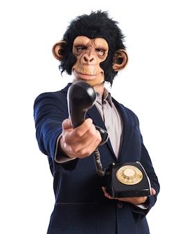 ヴィンテージの電話に話す猿の男