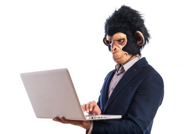Человек обезьяны с ноутбуком на белом фоне