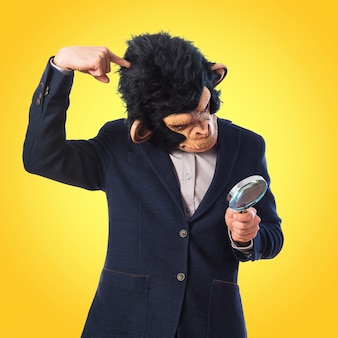 Человек обезьяны с увеличительным стеклом на цветном фоне Premium Фотографии