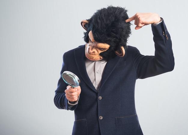 Человек обезьяны с лупой Premium Фотографии