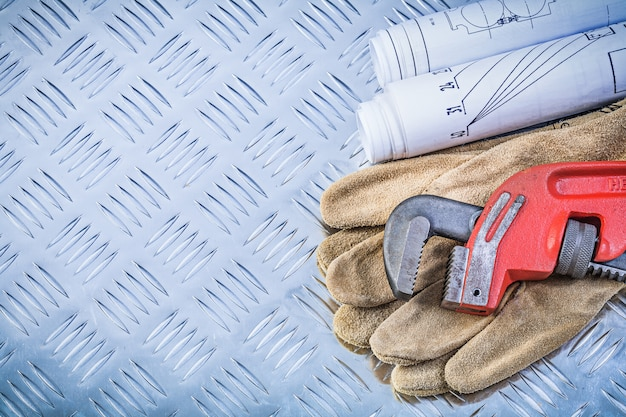 Monkey wrench blueprints safety gloves on grooved metal background construction concept