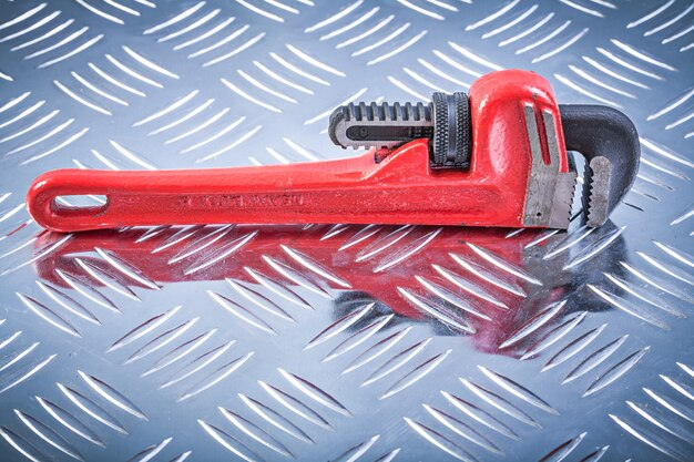 Monkey wrench on channeled metal background construction concept