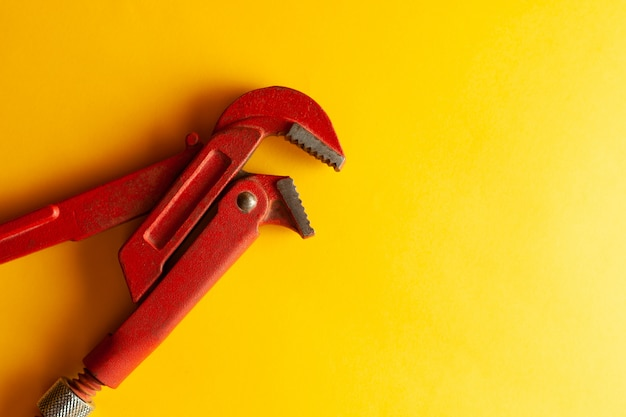 A monkey wrench on the yellow background with some fitting connectors. for design and decoration