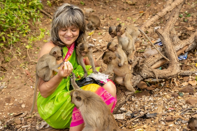 Monkeys surround a happy tourist who feeds them with fruit.