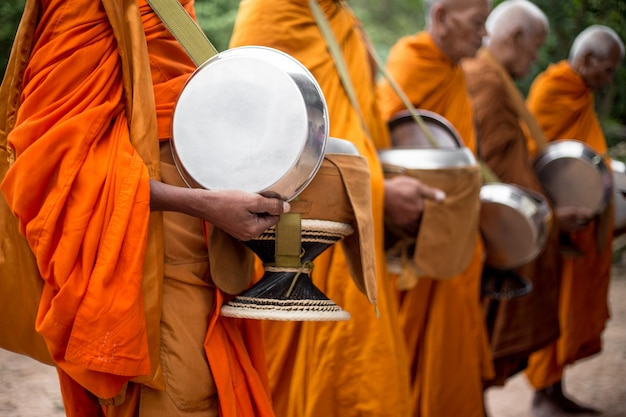 Monks alms round or receive food offerings moment.