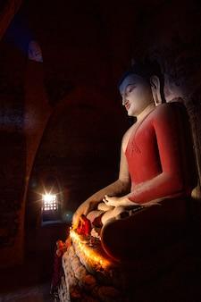 Монахи молятся статуе будды со свечами