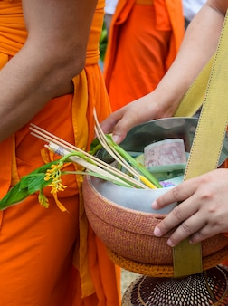 Monks receiving flower offering in tak bat dok mai or flower alms offering festival