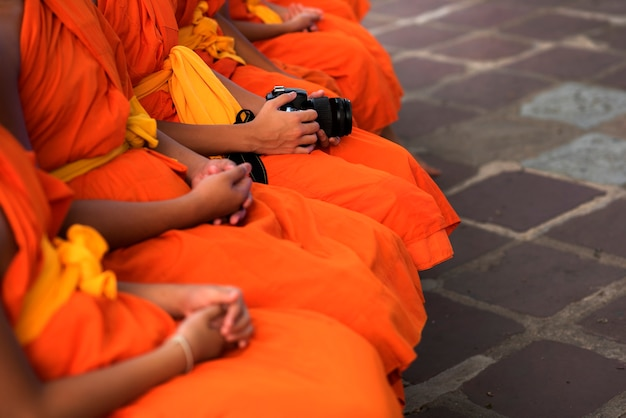 Monks sit orderly. and there's a camera nearby