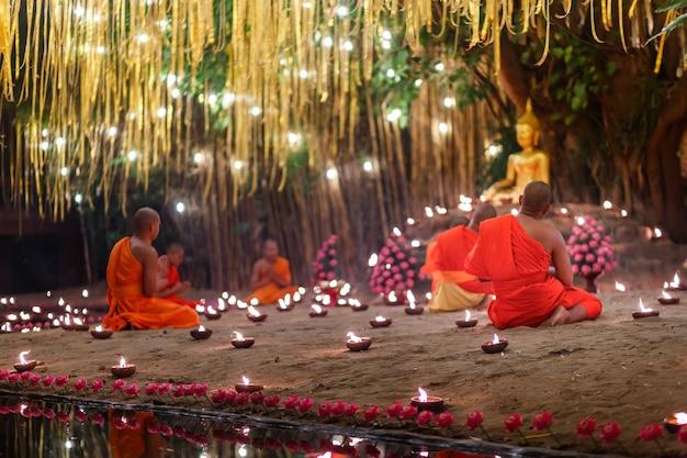 Сидящие монахи медитируют с множеством свечей в тайском храме ночью