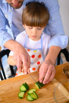 Mono-parental father and kid cutting cucumber