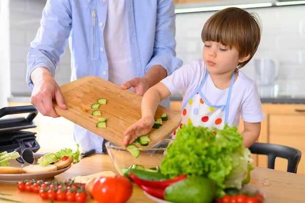 Mono-parental father and kid putting veggies in bowl