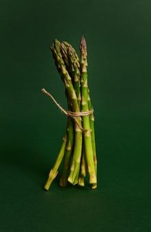 コピースペースで濃い緑色の背景に分離されたロープで結ばれたアスパラガスのシンプルな花束のモノクロ食品組成物。健康的な生のビーガンフード
