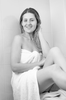 Monochrome image of beautiful woman with long hair covered in white towel sitting on bath