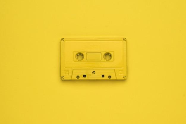 노란색 배경에 노란색 테이프 레코더의 흑백 이미지. 음악을 듣기 위한 세련된 복고풍 장비. 플랫 레이.