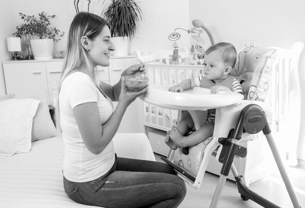 ハイチェアで彼女の男の子を養う美しい若い母親のモノクロ画像