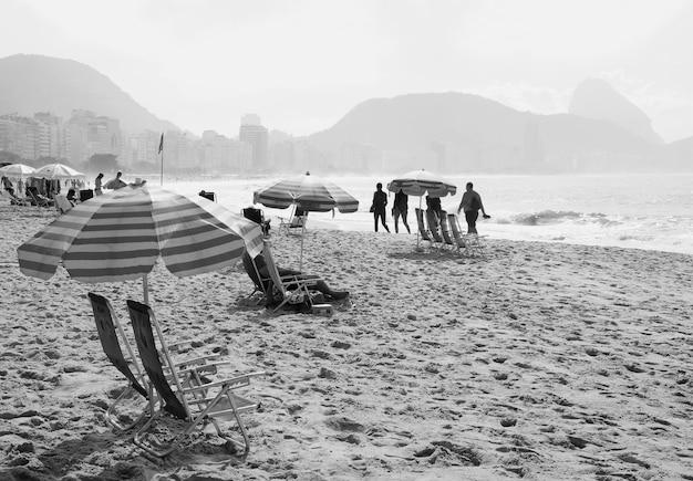 사람들의 그룹의 흑백 이미지는 모래 해변에서 활동을 즐깁니다.