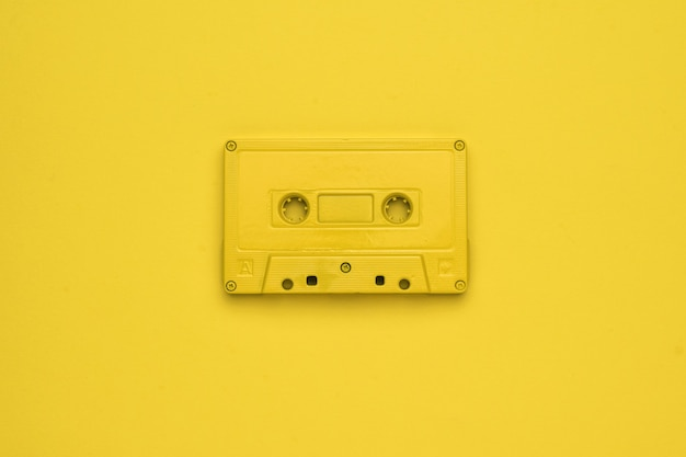Monochrome image of a yellow tape recorder on a yellow background. stylish retro equipment for listening to music. flat lay.