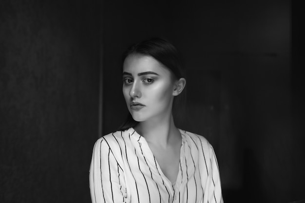 悲しい若いブルネットの女性のモノクロのインテリアの肖像画は、スタイリッシュな服を着ています。テキスト用のスペース