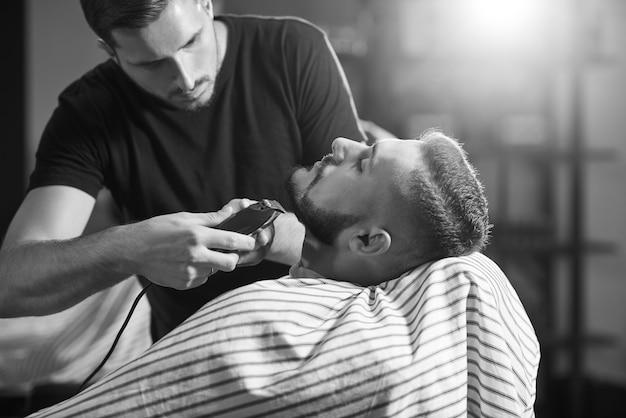 理髪店でひげを生やした若い男のモノクロームが彼のひげを形作り、トリミングしている