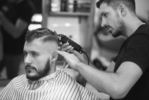 Монохромный профессиональный парикмахер с помощью машинки для стрижки во время работы