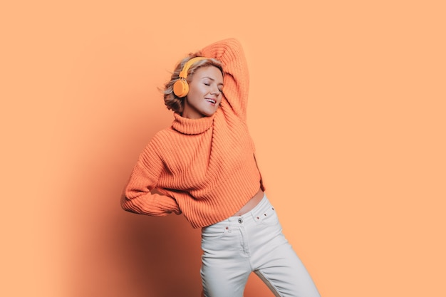 Monochrome photo of a caucasian woman listening to music on headphones posing on a orange wall