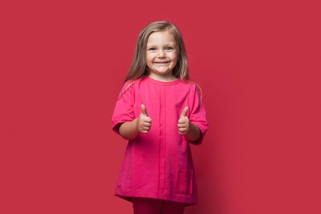 Монохромное фото блондинки, жестикулирующей знаком на красной стене, улыбаясь